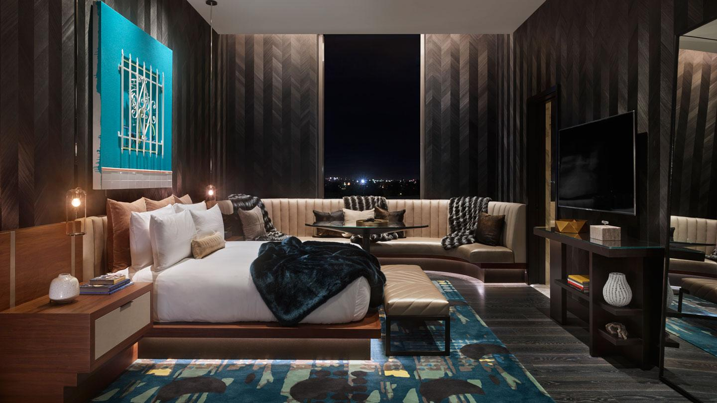 The mezzanine guest bedroom has a dark, muted palette with a chevron wood wall covering.