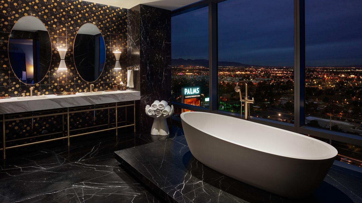 The King bedroom features pops of bronze and a black marble palette, with views of the city.