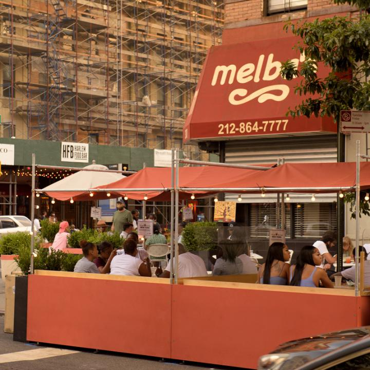 Street view of DineOut NYC outdoor dining booths outside of Melba's restaurant in Harlem