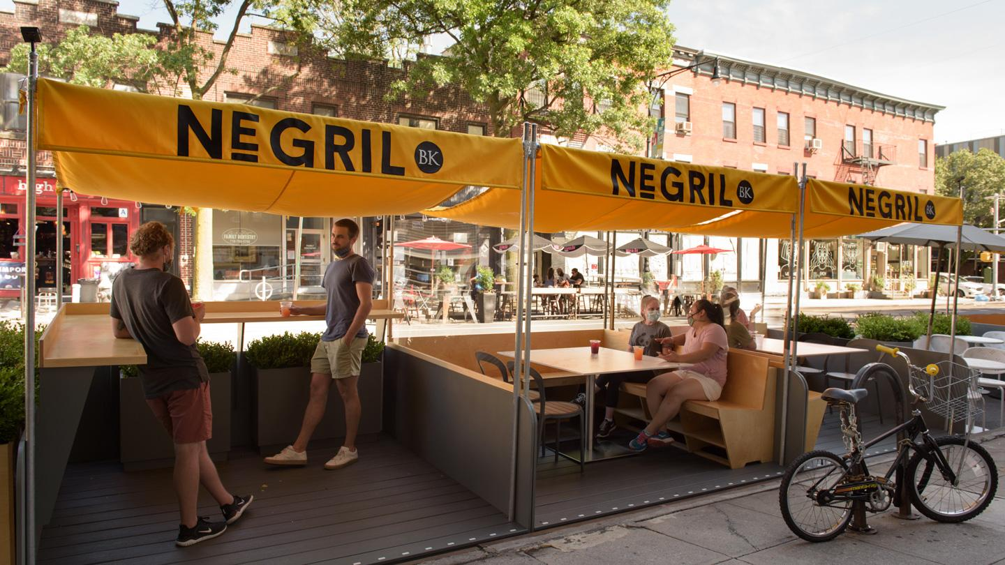 Four people hanging out in DineOut pavilions outside of Negril restaurant in Brooklyn