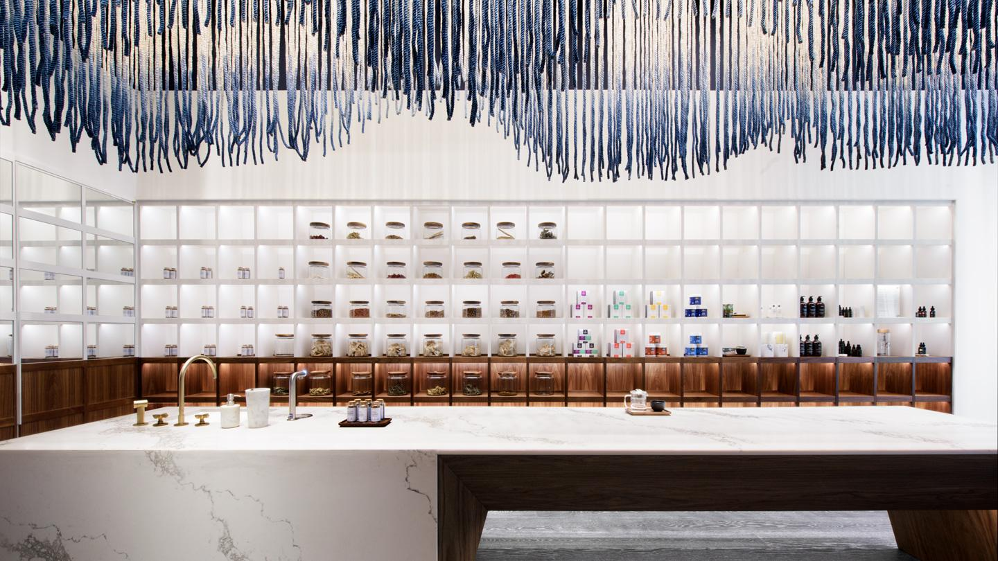 Shelving behind a a dip-dyed rope installation above a reception counter inside ORA